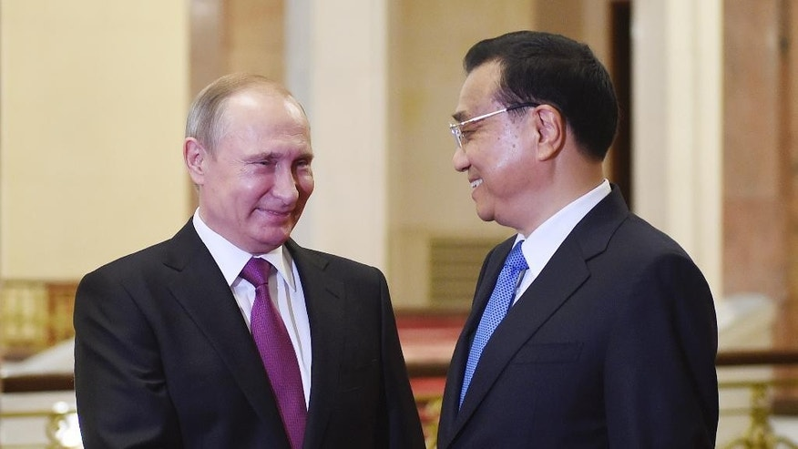 Russian President Vladimir Putin, left, is greeted by Chinese Premier Li Keqiang in Beijing's Great Hall of the People on Saturday, June 25, 2016. (Greg Baker/Pool Photo via AP)
