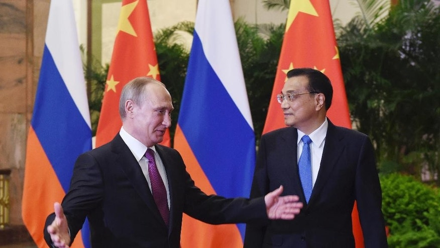Russian President Vladimir Putin, left, walks with Chinese Premier Li Keqiang before a meeting in Beijing's Great Hall of the People on Saturday, June 25, 2016. (Greg Baker/Pool Photo via AP)
