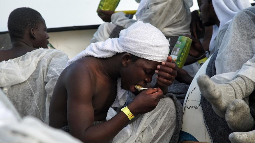 A migrant eats a hot meal as they rest aboard the 'Aquarius' rescue ship in the Mediterranean Sea Saturday June 25, 2016, as more than 600 migrants are aboard the ship rescued by SOS Mediterranee and the medical aid group Medecins Sans Frontieres (MSF). The organizations cooperate during search and rescue operations for migrants and refugees from boats in distress in the Mediterranean Sea. (AP Photo/Bram Janssen)