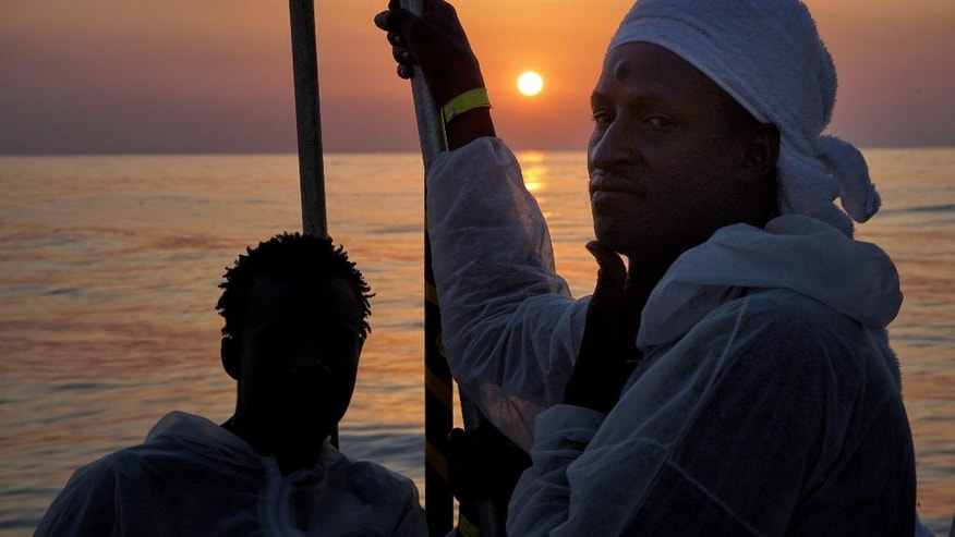 Migrants look out from the 'Aquarius' rescue vessel in the Mediterranean Sea Saturday June 25, 2016, as more than 600 migrants are aboard the ship rescued by SOS Mediterranee and the medical aid group Medecins Sans Frontieres (MSF). The organizations cooperate during search and rescue operations for migrants and refugees from boats in distress in the Mediterranean Sea. (AP Photo/Bram Janssen)
