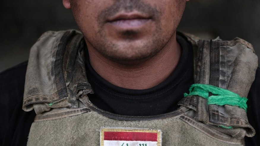 "In this Wednesday, June 8, 2016 photo, 1st Sgt. Malik Jaber, from Iraq's elite counterterrorism forces wears green cloth from the revered Imam Abbas shrine on his body armor, at a front line position on the southern edge of Fallujah, Iraq. He says he credits the holy object with saving his life when the Special Forces were fighting Islamic State militants in Beiji, the central Iraqi town that is also home to a key oil refinery. ""This time it will keep me safe again,"" Jaber said, ""God willing."" A senior Iraqi commander declared that the city of Fallujah was ""fully liberated"" from Islamic State group militants on Sunday, June 26, 2016 after a more than monthlong military operation. (AP Photo/Maya Alleruzzo)"