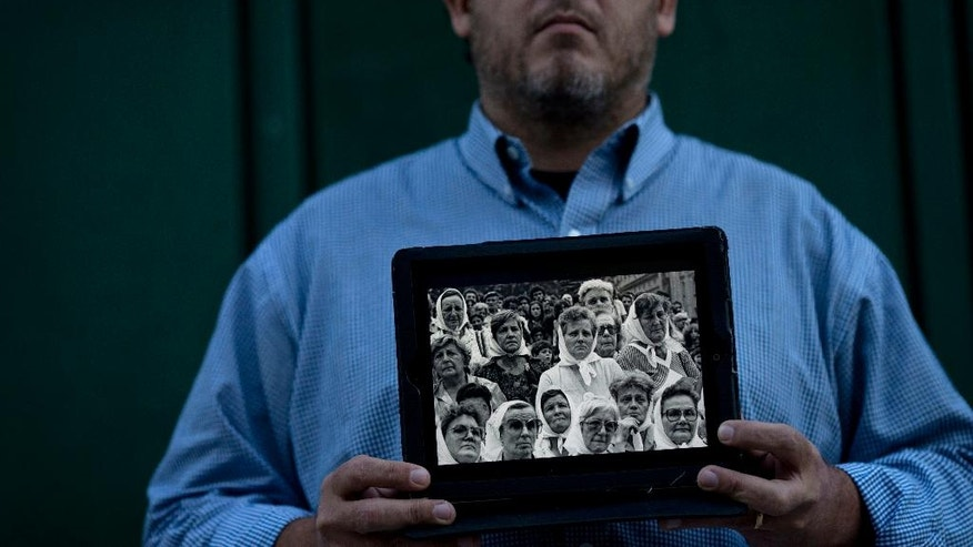 In this May 11, 2016 photo, Pedro Sandoval, who was stolen as a baby, poses holding a framed image of the Grandmothers of Plaza de Mayo group, that include both of his biological grandmothers, who helped him recover his true identity, in Buenos Aires, Argentina. Sandoval stopped celebrating Mother's Day, Father's Day and even his own birthday after he found out the truth: The mom and dad he knew growing up had stolen him from his biological parents, who were kidnapped, tortured and never heard from again during Argentina's 1976-1983 military dictatorship. (AP Photo/Natacha Pisarenko)