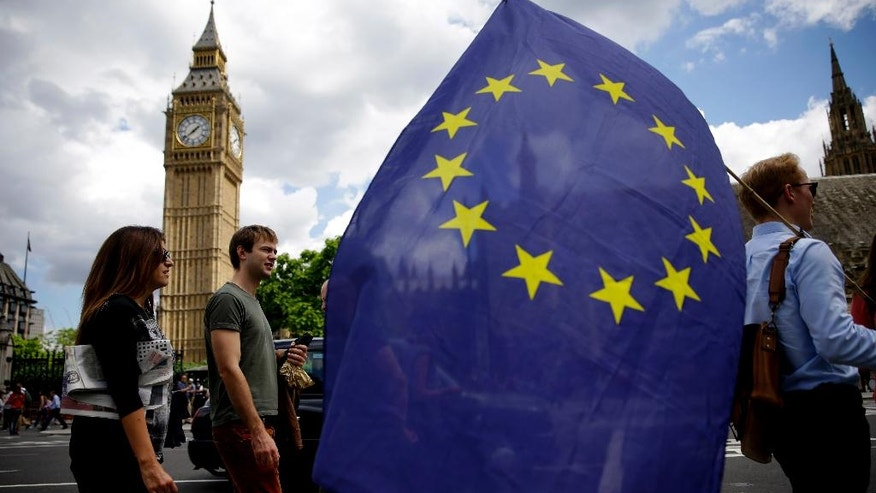 A remain supporter stops to talk to people as he walks around with his European flag across the street from the Houses of Parliament in London, Friday, June 24, 2016. Britain's Prime Minister David Cameron announced Friday that he will quit as Prime Minister following a defeat in the referendum which ended with a vote for Britain to leave the European Union. (AP Photo/Matt Dunham)