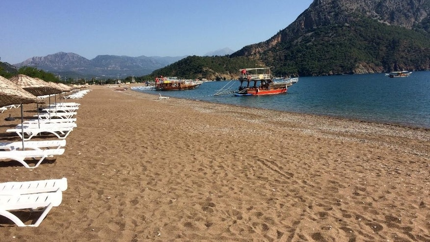 FILE - In this June 1, 2016 file photo, boats wait for tourists in Adrasan in Olympos area, about 100 kilometers west of Antalya, Turkey. Turkey's state-run news agency says authorities are evacuating residents and tourists from Olimpos village, 7 kilometers from behind the mountain in this picture, that is threatened by a forest fire. Anadolu Agency says the fire which broke out near the resort of Adrasan on Sunday was spreading toward the nearby retreat of Olimpos, fanned by winds.(AP Photo/Burhan Ozbilici, FILE)