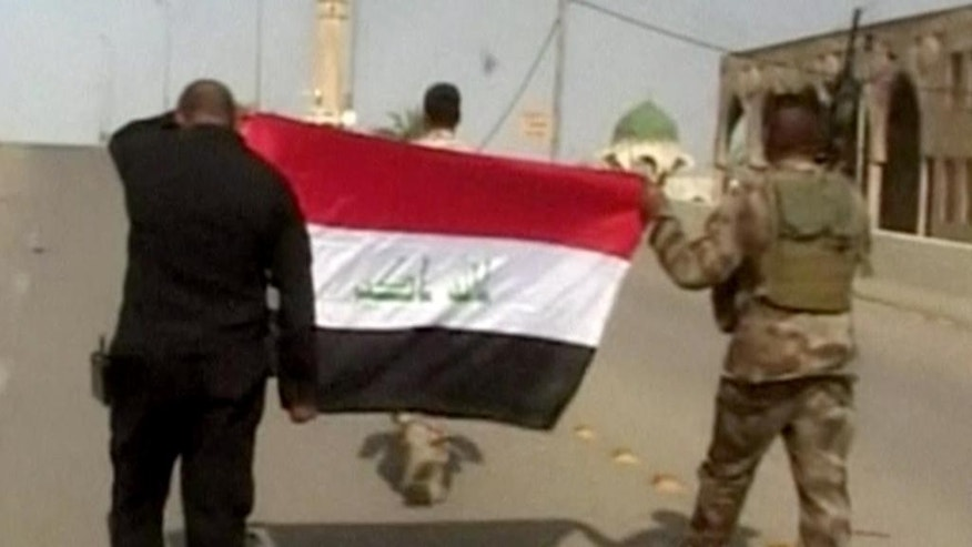 "This image made from Associated Press video shows, Iraqi soldiers carrying an Iraqi flag to hoist on buildings after a senior Iraqi commander declared that the city of Fallujah was ""fully liberated"" from Islamic State group militants, in Fallujah, Iraq, Sunday, June 26, 2016. (AP Video via AP)"