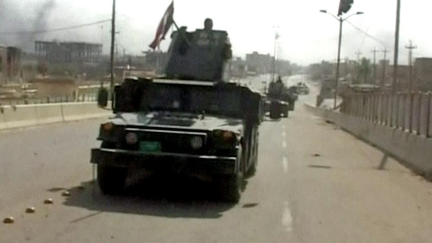 "This image made from Associated Press video shows, Iraqi troop carry an Iraqi flags on their tanks after a senior Iraqi commander declared that the city of Fallujah was ""fully liberated"" from Islamic State group militants, in Fallujah, Iraq, Sunday, June 26, 2016. (AP Video via AP)"