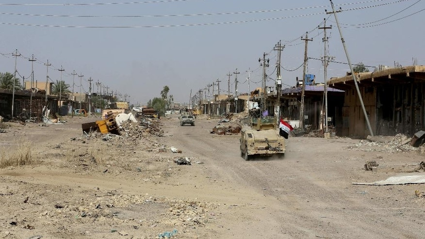 In this Wednesday, June 22, 2016 photo, Iraqi forces advance in Fallujah, Iraq. On the northwestern edge of Fallujah, Iraqi commanders are preparing for one of their toughest battles yet, despite declaring victory in the city west of Baghdad last week.(AP Photo/Hadi Mizban)