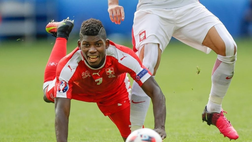 Switzerland's Breel Embolo falls in front of Poland's Grzegorz Krychowiak during the Euro 2016 round of 16 soccer match between Switzerland and Poland, at the Geoffroy Guichard stadium in Saint-Etienne, France, Saturday, June 25, 2016. (AP Photo/Pavel Golovkin)