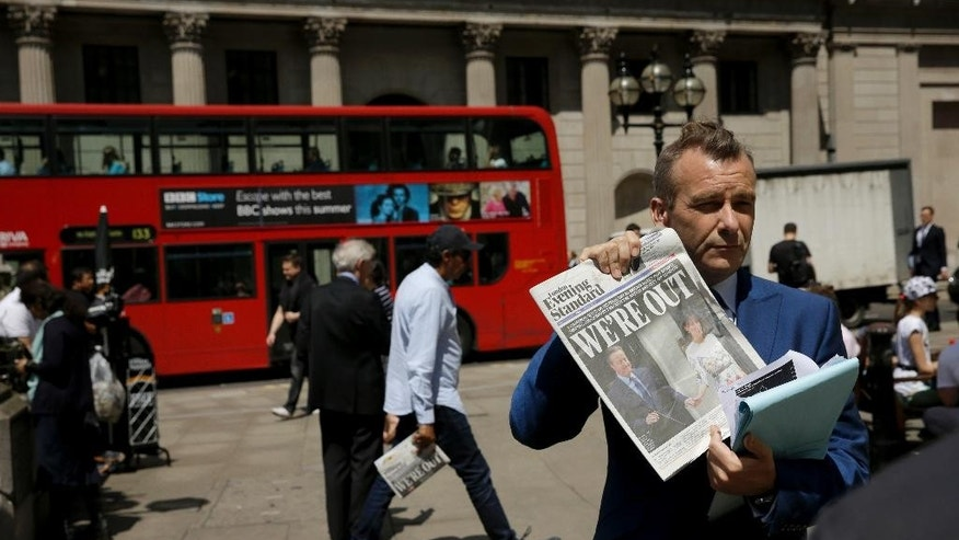 A journalist holds up a copy of the London Evening Standard newspaper as he takes part in a television broadcast outside the Bank of England in the City of London, Friday, June 24, 2016. Britain's Prime Minister David Cameron announced Friday that he will quit as Prime Minister following a defeat in the referendum which ended with a vote for Britain to leave the European Union. (AP Photo/Matt Dunham)