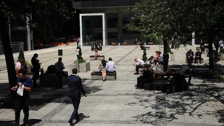 People sit in a square during lunchtime in the City of London, Friday, June 24, 2016. Britain's Prime Minister David Cameron announced Friday that he will quit as Prime Minister following a defeat in the referendum which ended with a vote for Britain to leave the European Union. (AP Photo/Matt Dunham)