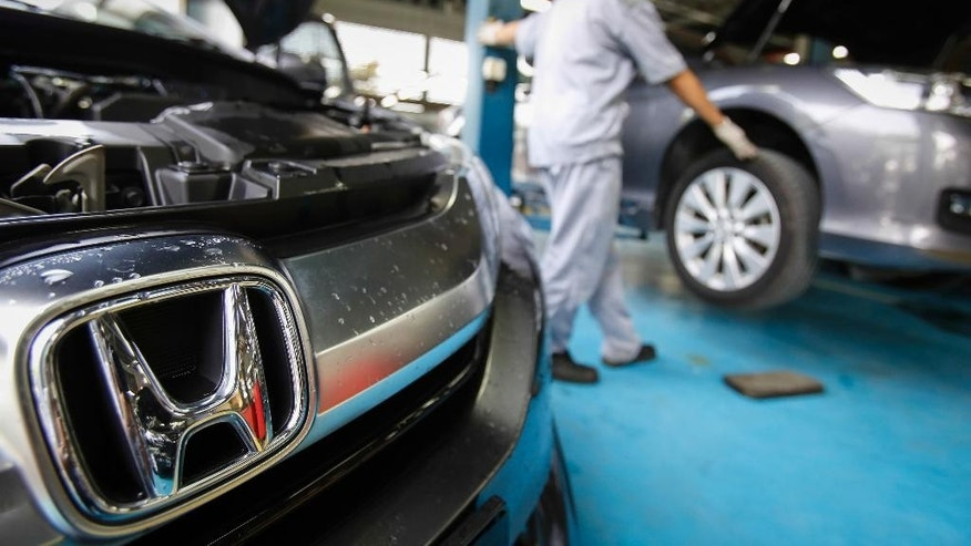 An automotive technician works on a Honda car at a service centre in Kuala Lumpur, Malaysia, Monday, June 27, 2016. A Malaysian woman has died after the airbag in her Honda City ruptured in a minor collision, a safety official said Monday. (AP Photo/Joshua Paul)
