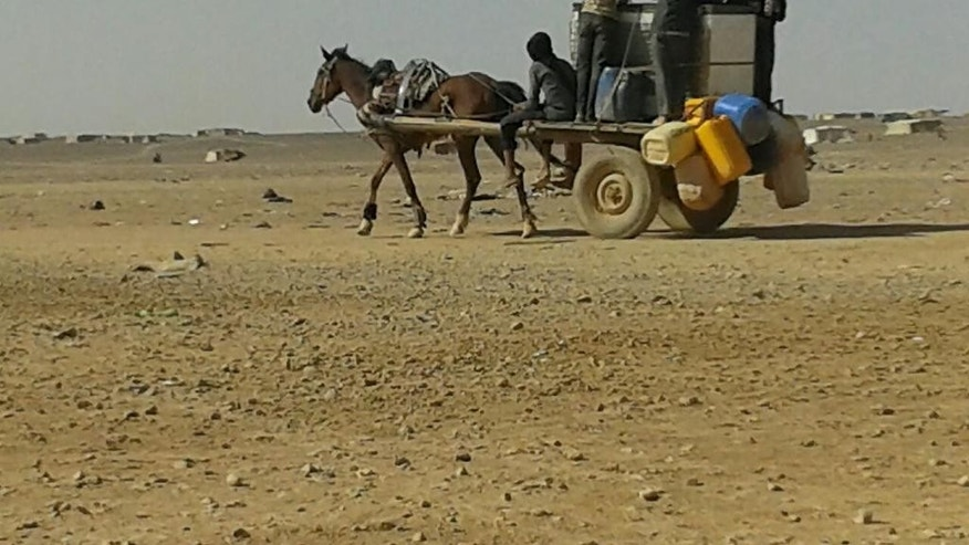In this Saturday, June 25, 2016 photo, Syrian refugees ride a donkey cart full of water bottles at the Ruqban border camp in northeast Jordan. Syrian refugees and international aid officials say little water and no food has reached 64,000 Syrian refugees stranded in the desert since Jordan sealed its border last week in response to a suicide attack.(AP Photo)