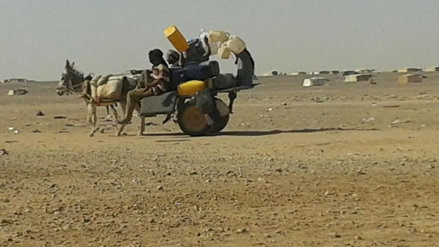 In this Saturday, June 25, 2016 photo, a Syrian refugee rides a donkey cart full of water bottles at the Ruqban border camp in northeast Jordan. Syrian refugees and international aid officials say little water and no food has reached 64,000 Syrian refugees stranded in the desert since Jordan sealed its border last week in response to a suicide attack. (AP Photo)