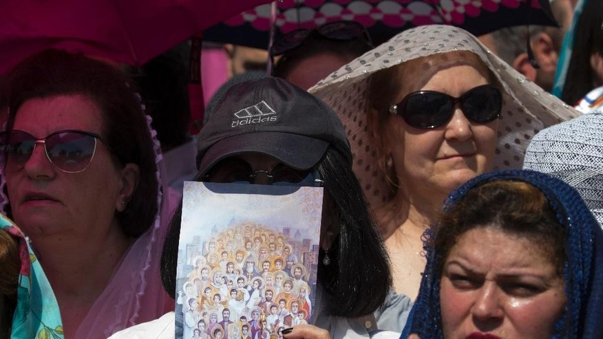 "A woman holds the ""Holy Martyrs"" icon, created by Tigran Barkhanajian on the occasion of the Canonization of the martyrs of the Armenian Genocide, during an open-air liturgy conducted by Catholicos Karekin II , attended by Pope Francis at the Armenian Apostolic Cathedral in Etchmiadzin, the seat of the Oriental Orthodox church outside Yerevan, Armenia, Sunday, June 26, 2016. Pope Francis wrapped up his trip to Armenia on Sunday with an open-air liturgy and a visit to the Orthodox country's closed border with Turkey amid new tensions with Ankara over his recognition of the 1915 ""genocide."" (AP Photo/Alexander Zemlianichenko)"