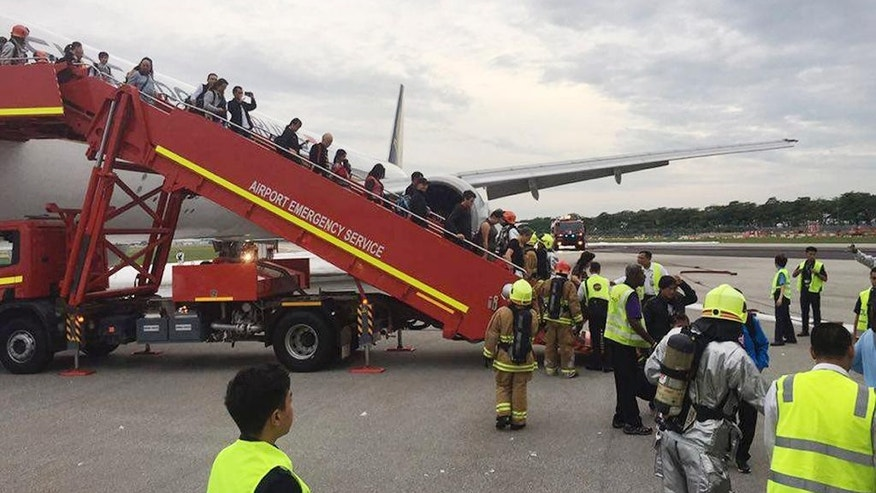 "This image provided by Lee Bee Yee shows passengers disembarking a Singapore Airlines flight after an engine fire, at Changi International Airport in Singapore on Monday, June 27, 2016. A Singapore Airlines statement said the Boeing 777-300ER was on its way to Milan when it turned back ""following an engine oil warning message."" It says the aircraft's right engine caught fire after Flight SQ368 touched down more than four hours after takeoff. (Lee Bee Yee via AP) MANDATORY CREDIT"