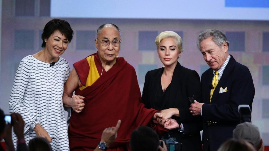 Journalist Ann Curry, from left, the Dalai Lama, Lady Gaga and businessman and philanthropist Philip Anschutz pose for a photo following a question and answer session at the U.S. Conference of Mayors in Indianapolis, Sunday, June 26, 2016. (AP Photo/Michael Conroy)