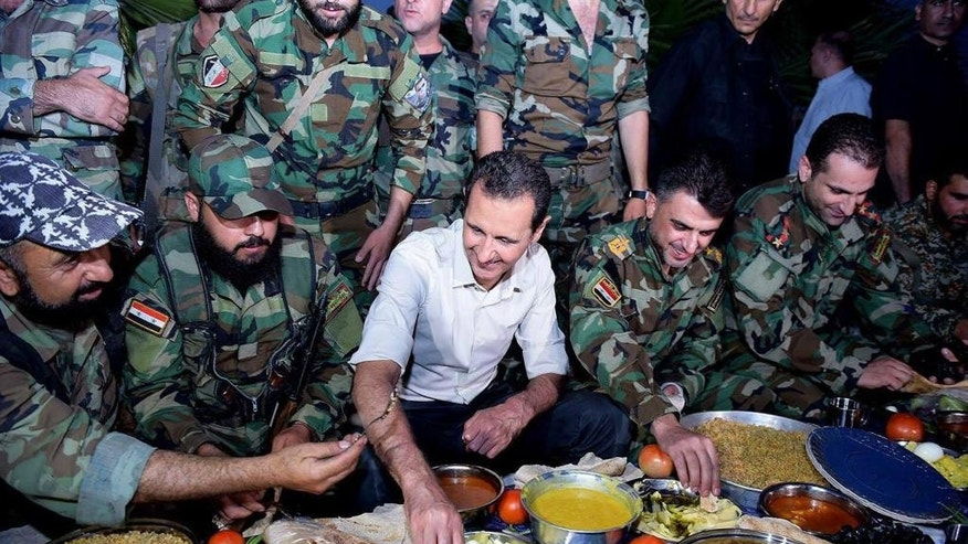 In this photo released on Sunday, June 26, 2016, by the Syrian official news agency SANA, Syrian President Bashar Assad, center, sits with Syrian troops as they break the Ramadan fast during his visit to the front line in the Damascus suburb of Marj al-Sultan, Syria. (SANA via AP)