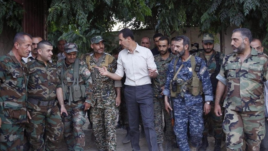 In this photo released on Sunday, June 26, 2016, by the Syrian official news agency SANA, Syrian President Bashar Assad, center, speaks with Syrian troops during his visit to the front line in the Damascus suburb of Marj al-Sultan, Syria. (SANA via AP)