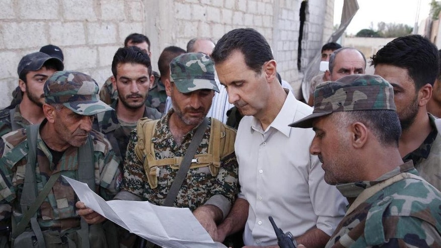 In this photo released on Sunday, June 26, 2016, by the Syrian official news agency SANA, Syrian President Bashar Assad, second right, speaks with Syrian troops during his visit to the front line in the Damascus suburb of Marj al-Sultan, Syria. (SANA via AP)