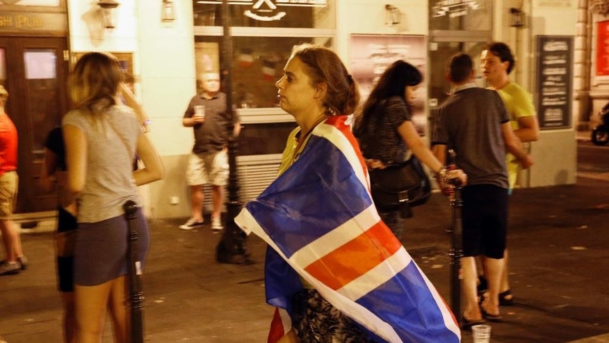 CORRECTS THE COUNTRY OF THE FLAG TO ICELAND INSTEAD OF BRITAIN - A soccer supporter walks wrapped in the flag of Iceland in Nice, France, Monday, June 27, 2016, after the Euro 2016 round of 16 soccer match between England and Iceland. England was defeated 2-1. (AP Photo/Darko Bandic)