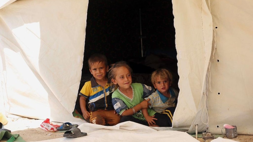 In this picture taken Saturday, June 25, 2016, internally displaced children from Fallujah, who fled their homes during fighting between Iraqi security forces and the Islamic State group, at a camp at Amariyat Fallujah, Iraq. Tens of thousands of Iraqis who survived a harrowing flight from Fallujah now find themselves in sprawling desert camps with little food, water or shelter. The growing humanitarian crisis less than an hour's drive from Baghdad has reinforced the region's deep-seated distrust of the government, and could undermine recent gains against the Islamic State group. (AP Photo/ Khalid Mohammed)