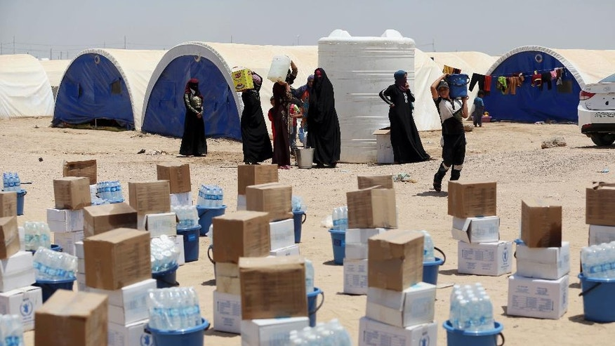 In this picture taken Saturday, June 25, 2016, internally displaced civilians from Fallujah, who fled their homes during fighting between Iraqi security forces and the Islamic State group, at a camp at Amariyat Fallujah, Iraq. Tens of thousands of Iraqis who survived a harrowing flight from Fallujah now find themselves in sprawling desert camps with little food, water or shelter. The growing humanitarian crisis less than an hour's drive from Baghdad has reinforced the region's deep-seated distrust of the government, and could undermine recent gains against the Islamic State group. (AP Photo/ Khalid Mohammed)