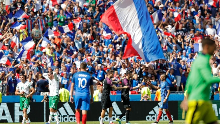 Players leave the pitch at the end of the Euro 2016 round of 16 soccer match between France and Ireland, at the Grand Stade in Decines-­Charpieu, near Lyon, France, Sunday, June 26, 2016. France won 2-1. (AP Photo/Laurent Cipriani)