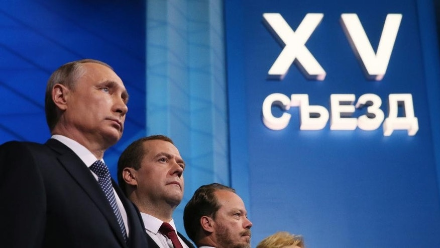 Russian President Vladimir Putin, left, and Prime Minister Dmitry Medvedev, center, listen to the national anthem at the United Russia party congress which is being held three months ahead of parliamentary elections, in Moscow, Russia, Monday, June 27, 2016. (Yekaterina Shtukina/ Pool photo via AP)