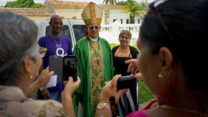 In this June 19, 2016 photo, the new archbishop of Havana, Juan de la Caridad Garcia, poses for a photo with two parishioners outside the Saint John the Baptist church in Jaruco, Cuba. Garcia is expected to bring a different style to the Cuban Catholic Church in his new post, the most important religious position on the island. After three decades under Cardinal Jaime Ortega, a skilled international diplomat comfortable in the halls of power, the Cuban church will be led by a man focused intently on rebuilding the church by ministering to the least-privileged people of faith in one of Latin America's least observant countries. (AP Photo/Ramon Espinosa)