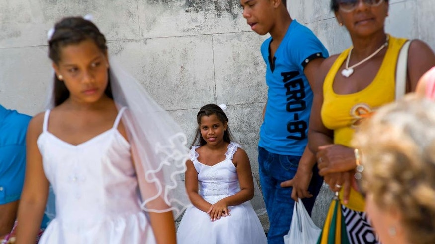 In this June 19, 2016 photo, the 10-year-old Ramos twin sisters, Michely, left, and Chavely, celebrate with family after receiving their first communion at a Mass celebrated by Havana's new archbishop at the Saint John the Baptist church in Jaruco, Cuba. Msgr. Juan de la Caridad Garcia left Havana's grand Cathedral to celebrate Mass at the town church in the central Mayabeque province. (AP Photo/Ramon Espinosa)