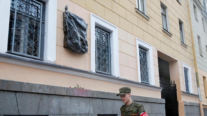 In this Sunday, June 26, 2016 photo a cadet walks past a plaque to Carl Mannerheim which is covered with plastic, in St.Petersburg, Russia. A plaque commemorating Carl Mannerheim in the Russian city of St. Petersburg has been splashed with red paint shortly after it was unveiled this month, highlighting the controversy over the Finnish soldier and statesman who served in the Imperial Russian Army but after the 1917 Bolshevik Revolution and Finland's declaration of independence took over command of Finnish troops and led Finland against the Soviet Union during World War II. (AP Photo/Dmitry Lovetsky)
