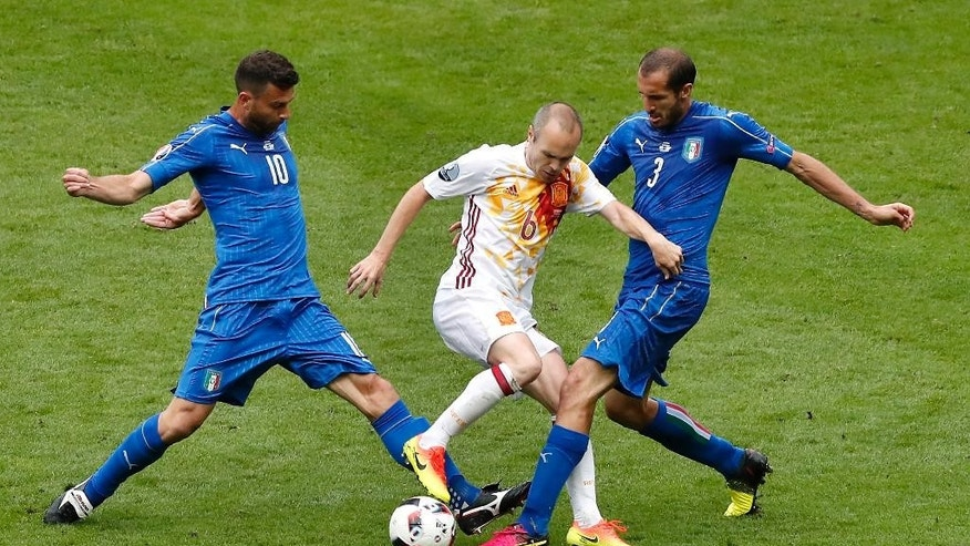 Spain's Andres Iniesta, center, challenges for the ball with Italy's Thiago Motta, left, and Giorgio Chiellini, right, during the Euro 2016 round of 16 soccer match between Italy and Spain, at the Stade de France, in Saint-Denis, north of Paris, Monday, June 27, 2016. (AP Photo/Francois Mori)