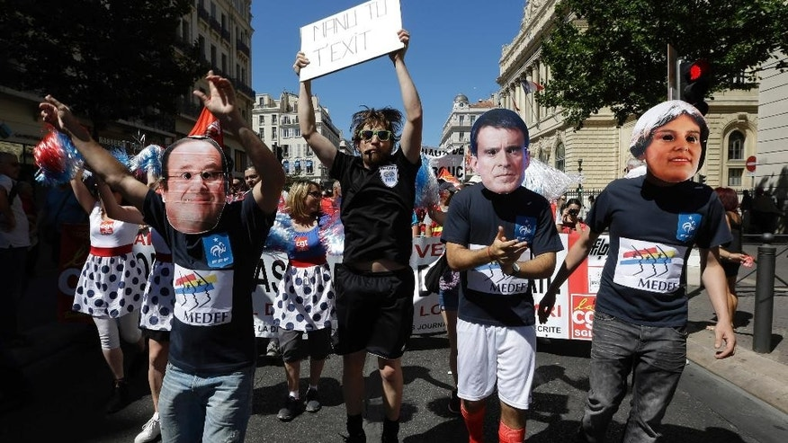 Protesters wearing the mask of French President Francois Hollande, left, French Prime Minister Manuel Valls and Labor Minister Myriam el Khomry demonstrate in Marseille, Tuesday, June 28, 2016. Protesters from numerous sectors planned a march in Paris later in the day, as the Senate votes on the controversial labor measure that would make France's 35-hour workweek longer and layoffs easier.  (AP Photo/Claude Paris)