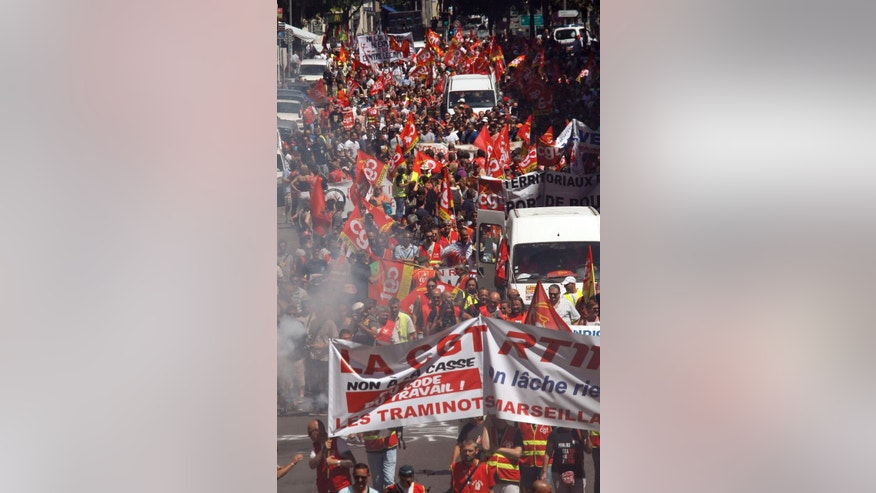 Workers  demonstrate in Marseille, Tuesday, June 28, 2016. Protesters from numerous sectors planned a march in Paris later in the day, as the Senate votes on the controversial labor measure that would make France's 35-hour workweek longer and layoffs easier.  (AP Photo/Claude Paris)