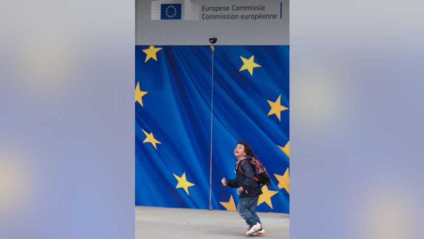 A small boy runs past a door with the EU flag logo at EU headquarters in Brussels on Tuesday, June 28, 2016. EU heads of state and government meet Tuesday and Wednesday in Brussels for the first time since Britain voted to leave the European Union, throwing British and European politics into disarray. (AP Photo/Virginia Mayo)