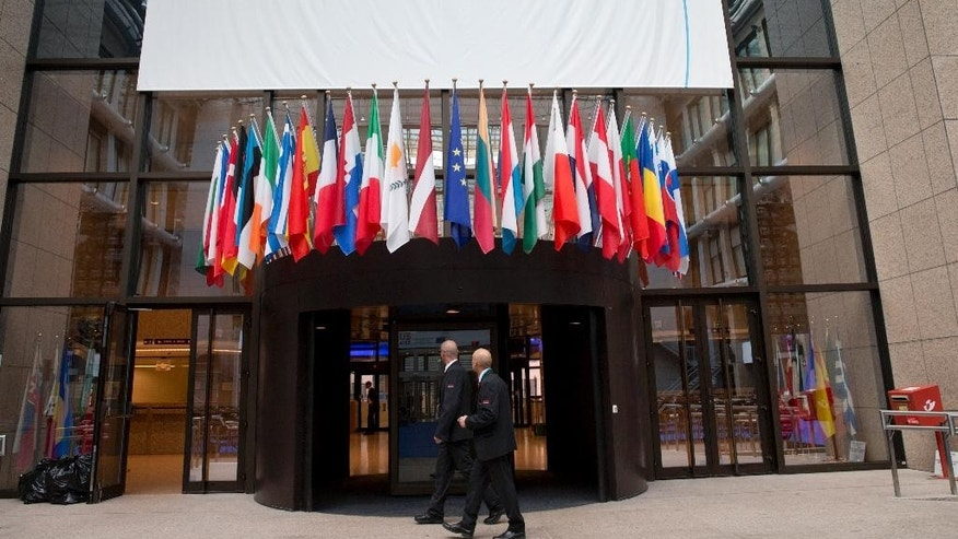 Two security officers walk by flags of EU nations prior to an EU summit in Brussels on Tuesday, June 28, 2016. EU heads of state and government meet Tuesday and Wednesday in Brussels for the first time since Britain voted to leave the European Union, throwing British and European politics into disarray. (AP Photo/Virginia Mayo)