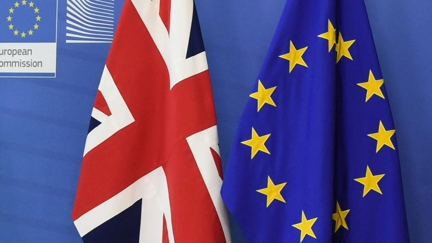 FILE -  This is Tuesday, Feb. 16, 2016 file photo of  the EU, right, and the British flags as they are placed next to each other at EU headquarters in Brussels. Nearly 1,000 British nationals who work for the European Union's executive have been assured their jobs are safe. ?  (AP Photo/Geert Vanden Wijngaert , File )