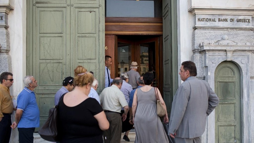 Athens residents enter a branch of the National Bank of Greece as it open it's gate in central Athens on Tuesday, June 28, 2016. Greece introduced capital controls for bank transactions a year ago amid financial turmoil triggered by bailout negotiation delays. Country residents can still withdraw a maximum of 420 euros (around $465) a week. (AP Photo/Petros Giannakouris)