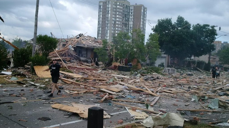 A police officer gestures while walking amongst debris littering a street after a house exploded in Mississauga, Ontario, Tuesday, June 28, 2016. Police are evacuating homes in the area as they investigate the explosion.  (Zeljko Zidaric/The Canadian Press via AP) MANDATORY CREDIT