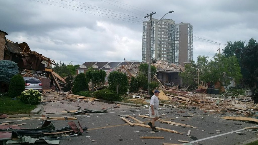 A man walks amongst debris littering a street after a house exploded in Mississauga, Ontario, Tuesday, June 28, 2016. Police are evacuating homes in the area as they investigate the explosion.  (Zeljko Zidaric/The Canadian Press via AP) MANDATORY CREDIT
