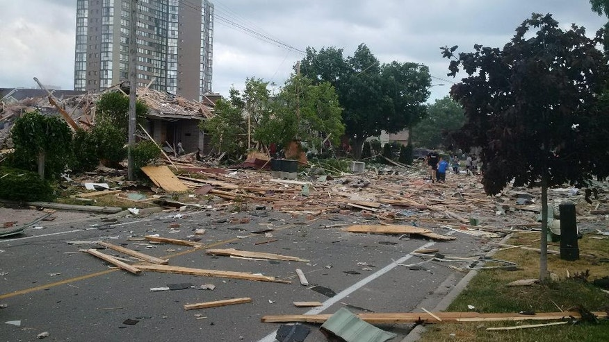 Debris litters a street after a house exploded in Mississauga, Ontario, Tuesday, June 28, 2016. Police are evacuating homes in the area as they investigate the explosion.  (Zeljko Zidaric/The Canadian Press via AP) MANDATORY CREDIT