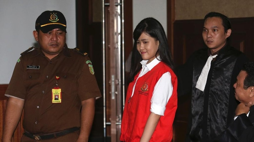 Jessica Kumala Wongso, center, who is accused of murdering her friend by lacing her coffee with cyanide,  enters the courtroom prior to the start of her trial hearing at Central Jakarta District Court in Jakarta, Indonesia, Tuesday, June, 28, 2016.  An Indonesian court has decided to proceed with the trial of the woman.  The 27-year-old defendant,  Wongso was charged with planning the Jan. 6 poisoning of Wayan Mirna Salihin because of the victim's advice that she sever her relationship with her troublesome boyfriend. The two were former classmates in Australia. (AP Photo/Tatan Syuflana)