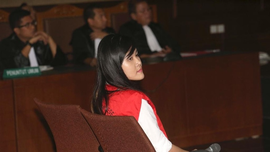 Jessica Kumala Wongso, center, who is accused of murdering her friend by poisoning her with cyanide sits on the defendant's chair during her trial hearing at Central Jakarta District Court in Jakarta, Indonesia, Tuesday, June, 28, 2016.   An Indonesian court has decided to proceed with the trial of the woman.  The 27-year-old defendant,  Wongso was charged with planning the Jan. 6 poisoning of Wayan Mirna Salihin because of the victim's advice that she sever her relationship with her troublesome boyfriend. The two were former classmates in Australia.(AP Photo/Tatan Syuflana)