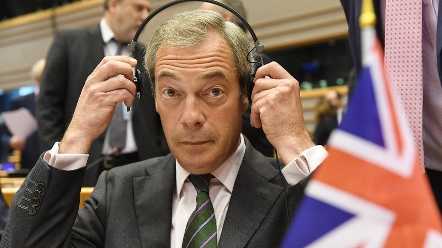 Leader of the UKIP Nigel Farage sits behind a British flag during a special session of European Parliament in Brussels on Tuesday, June 28, 2016. EU heads of state and government meet Tuesday and Wednesday in Brussels for the first time since Britain voted to leave the European Union, throwing British and European politics into disarray. (AP Photo/Geert Vanden Wijngaert)