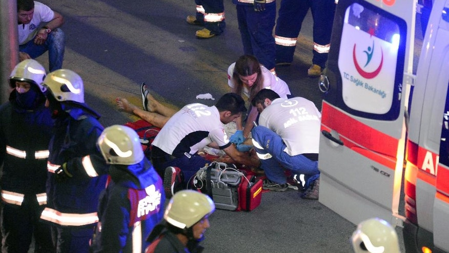 Turkish rescue services members help a wounded person outside Istanbul's Ataturk airport, Tuesday, June 28, 2016. Two explosions have rocked Istanbul's Ataturk airport, killing several people and wounding scores of others, Turkey's justice minister and another official said Tuesday. A Turkish official says two attackers have blown themselves up at the airport after police fired at them. The official said the attackers detonated the explosives at the entrance of the international terminal before entering the x-ray security check. (Ismail Coskun, IHA via AP) TURKEY OUT