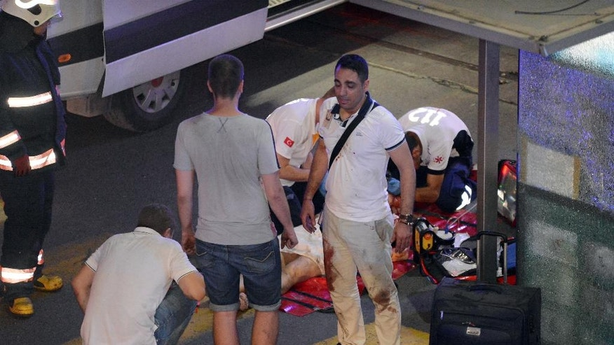 Turkish rescue services help a wounded person outside Ataturk Airport in Istanbul, Tuesday, June 28, 2016. Two explosions have rocked Istanbul's Ataturk airport, killing several people and wounding others, Turkey's justice minister and another official said Tuesday. A Turkish official says two attackers have blown themselves up at the airport after police fired at them. The official said the attackers detonated the explosives at the entrance of the international terminal before entering the x-ray security check. (Ismail Coskun, IHA via AP) TURKEY OUT