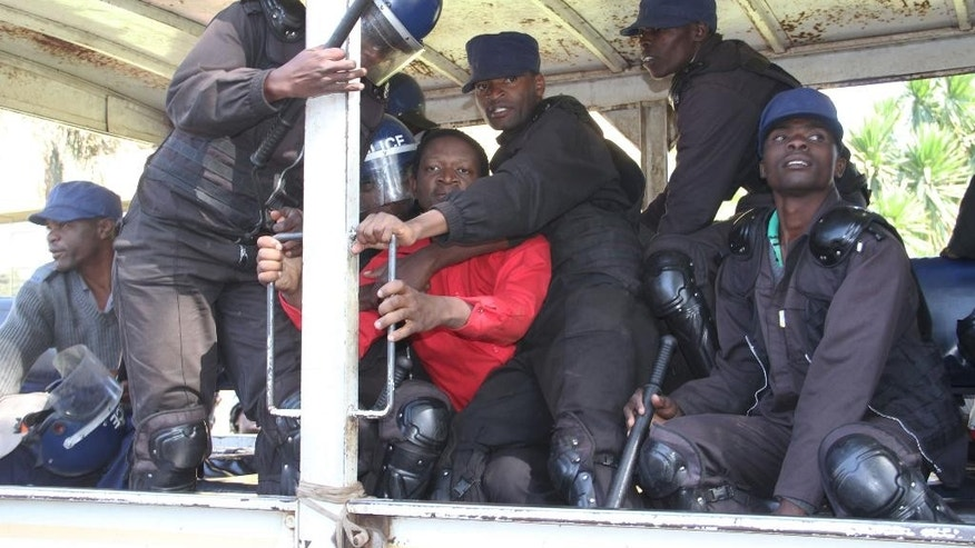 Zimbabwean activist Sten Zvorwadza, centre, is surrounded by police after he was detained following a protest at a local hotel in Harare, on Friday, June, 24, 2016.  Activists are protesting against Zimbabwean Vice President Phelekezela Mphokos who has stayed at the hotel for 18-months at 400 dollars a night in Harare. (AP Photo)