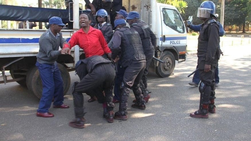 Zimbabwean activist Sten Zvorwadza,centre, is surrounded by police after he was arrested following a protest at a local hotel in Harare, in this Friday, June, 24, 2016 photo.Zvorwadza was joined by other activists angry at Zimbabwean Vice President Phelekezela Mphokos 18 month stay in a $400 - a night hotel suite in the capital Harare.The confrontation revealed the frustrations of many in a country where the economy contunues to plummet. (AP Photo)