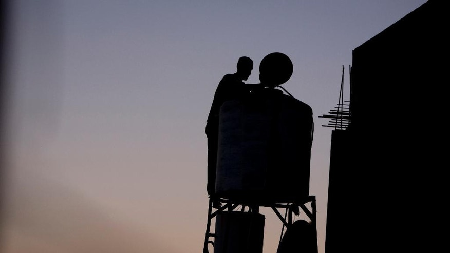 In this Saturday, June 18, 2016 photo, a Palestinian man checks the water tank on the roof of his home after water supply was cut in the village of Salem near the West Bank city of Nablus. Palestinians in the West Bank have long faced shortages of water in the summer months. But this year, as they fast dawn-to-dusk amid scorching heat during the Muslim holy month of Ramadan, many villagers in the north of the territory say Israel has intentionally cut the water flow to their taps. (AP Photo/ Majdi Mohammed)