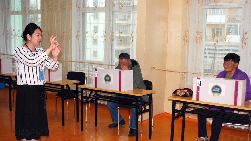 An election official explains the process of casting votes for residents at a polling station in Bayanzurkh district of Ulaanbaatar, Mongolia on Wednesday, June 29, 2016. Mongolians vote in parliamentary elections Wednesday with sentiment weighed by a sharp downturn in the landlocked Asian nation's crucial mining sector, rising unemployment and political disillusionment. (AP Photo/Ganbat Namjilsangarav)